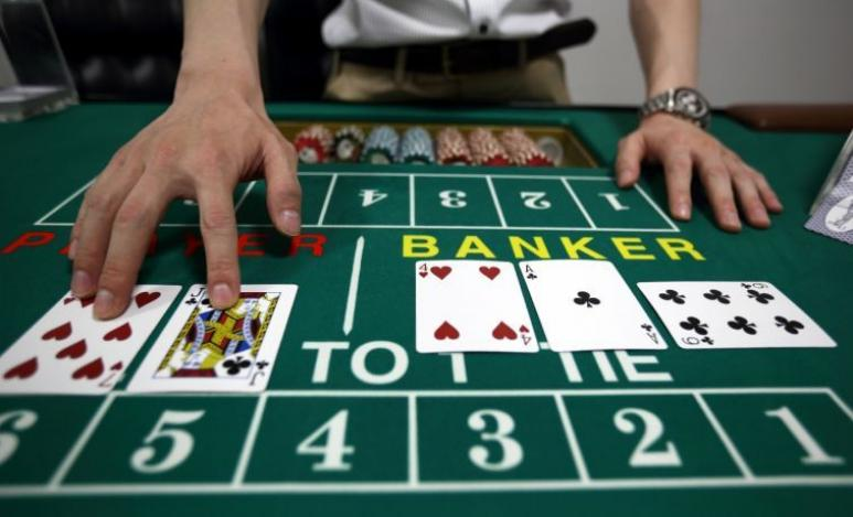 baccarat table and live dealer with cards